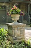 11930061-Stone-planter-with-flowers-near-driveway-of-house-Stock-Photo