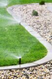 26608652-Automatic-sprinklers-watering-grass-Stock-Photo