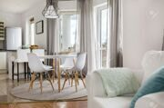 63502531-New-flat-with-round-table-white-chairs-and-open-kitchen-Stock-Photo